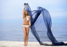 年轻人、适合和美丽的妇女海滩跳舞的与丝绸 免版税库存照片