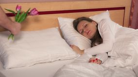 人丈夫手在床上的枕头近睡觉的女性妇女上把郁金香花放 股票录像