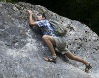 年轻人上升的岩石 图库摄影