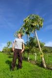 人下个木瓜突出对结构树年轻人 图库摄影