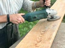 人与他的手一起使用,为研磨机,为研和擦亮表面的电工具研盘  库存图片