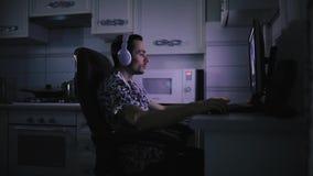 人与他的编辑在黑暗的厨房室,蓝色轻的屏幕的录影一起使用 股票录像