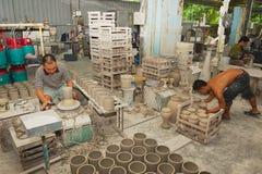 人与传统纪念品生产的白陶土一起使用在一个车间在古晋,马来西亚 免版税库存照片