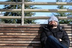 人与冬天穿衣,坐与雪的一个长木凳 免版税库存图片