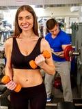 人与哑铃一起使用在健身房 库存图片