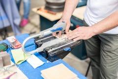 人与夹具锯一起使用 Fretsaw工具固定式固定在桌上 做与电锯工具的人木图 库存照片