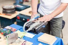 人与夹具锯一起使用 Fretsaw工具固定式固定在桌上 做与电锯工具的人木图 图库摄影
