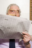 人与放大镜的读书报纸 免版税库存照片
