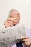 人与放大镜的读书报纸 库存图片