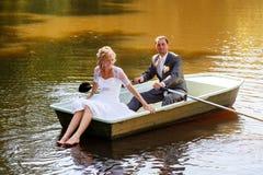 年轻人与新娘和新郎结婚在小船 免版税库存照片