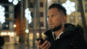 人与智能手机的语音识别在公园夜室外旅馆的酒吧,学生男性用途消息音频帮手发现者在 股票视频