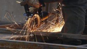 人与研磨机一起使用 在工厂削减钢结构 美丽的火花飞行  股票录像