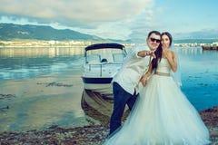 年轻人与站立在小船附近的夫妇结婚在婚礼礼服和衣服的海边 免版税库存图片