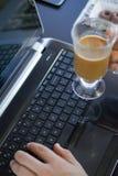 人与膝上型计算机和咖啡一起使用 免版税库存照片