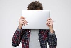 年轻人与膝上型计算机的覆盖物面孔 库存图片
