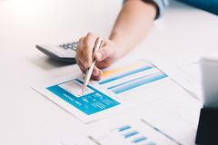 人与计算的数字计算器一起使用 费用计算器,贷款投资文件 财政和就职 免版税图库摄影