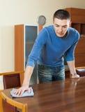 人与洗涤剂擦亮剂的打扫灰尘桌在家 免版税图库摄影