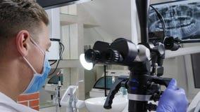 人专家与在下颌前面的光学显微镜一起使用在显示器在牙医` s办公室
