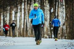 人中年赛跑者在路多雪的公园运行 库存图片