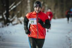 人中年赛跑者通过多雪的公园胡同运行在12月 免版税库存图片