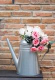 人为在金属花瓶上升了 免版税库存照片