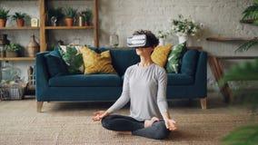 人为现实玻璃的亭亭玉立的小姐在莲花姿势在家思考用在namaste享用的手 股票视频