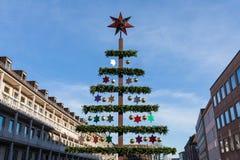 人为艺术家圣诞树在有蓝天的一个城市 免版税库存照片