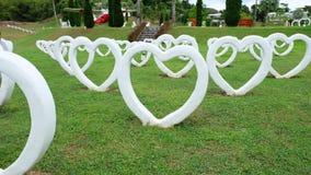 人为水泥白色心脏的形状,修造在草绿色背景 免版税库存照片