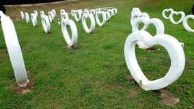 人为水泥白色心脏的形状,修造在草绿色背景 免版税库存图片