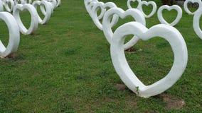 人为水泥白色心脏的形状,修造在草绿色背景 图库摄影