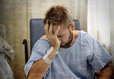 年轻人为他的卫生状况在医房伤害了人单独坐在痛苦中担心的 免版税图库摄影