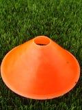 人为绿色塑料草在与明亮的橙色塑料锥体的背景中 在冬天footbal操场的标记 库存图片