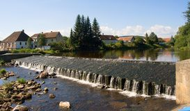 人为水闸和村庄奥塔瓦河河的,飞溅结冰的水,捷克秀丽  免版税库存图片