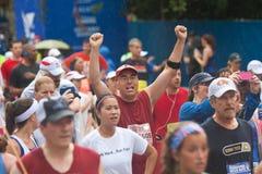 人举胜利地完成亚特兰大10K公路赛的胳膊 免版税库存图片