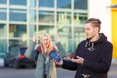 人举行一个残破的手机、女孩尖叫在背景中和姿态用她的手 免版税库存照片