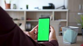 人举行与绿色屏幕色度嘲笑的一smarpthone 股票录像