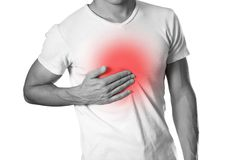 人举行他的胸口胸口痛 胃灼热 壁炉边 免版税图库摄影