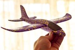 人举行儿童的塑料飞机和梦想成为飞行员 ?? 库存照片