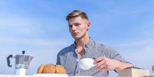 人举行咖啡天空背景 人肌肉运动员饮料早晨咖啡 宜人的早晨户外 每日 免版税库存图片