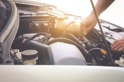 人举行在离开前的油检查汽车安全的 免版税库存照片