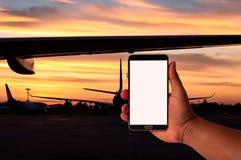 人举行手机的手在被弄脏的飞机停车处的与暮色天空期间 免版税库存图片