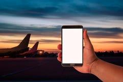 人举行手机的手在被弄脏的飞机停车处的与暮色天空期间 图库摄影