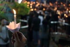 人举行烛光焰光的手在晚上有bokeh背景 库存图片