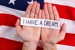 人举行的手题字我有一个梦想,以美国国旗为背景 免版税库存照片