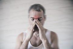 人举行他的与手指的鼻子和静脉窦区域在从头痛的明显的痛苦中在前面前额区域 免版税库存图片