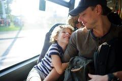 年轻人乘公共汽车去与儿子一起 库存图片