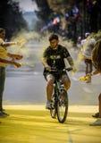 人乘在颜色奔跑事件的自行车 免版税图库摄影