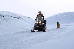 人乘坐在小丘中的一辆雪上电车,陪同由猎狗 免版税库存图片
