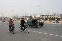 人乘坐的自行车在中国和一辆动力化的公共自行车 库存照片