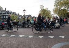 人乘坐的自行车通过阿姆斯特丹街道  自行车是populat运输在阿姆斯特丹 免版税库存图片